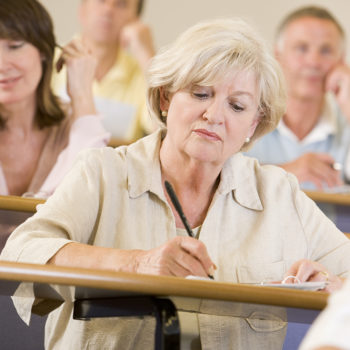 Woman sitting in adult classroom taking notes with students in background (selective focus)
